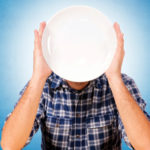 Man holding plate in front of his face