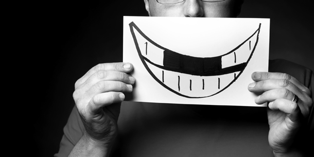 Man holding a drawing of a smile in front of his face