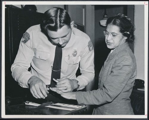 Rosa Parks being fingerprinted in a police station.