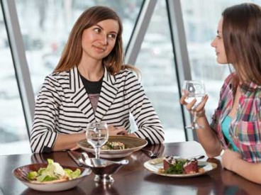 Two women talking at lunch. Source: Shutterstock.com/Evstigneev Alexander