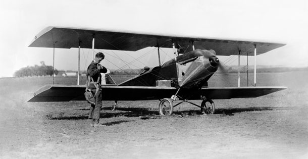 Charles Lindbergh adjusts his parachute in front of Sergeant Bell's experimental biplane on Lambert Field, St. Louis, Missouri, in the mid-to-late 1920s, while Bell waits in the plane.
