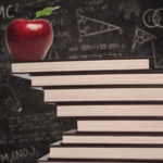 Apple education symbol and stack of books in classroom with written board