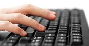 Hand typing at keyboard. Photo by Tyler Olson via Shutterstock.