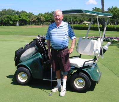 Bill Hefferon standing next to a golf cart.