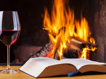 book and full wineglass in front of fireplace