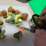 dipping broccoli in spice mixture