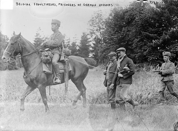 Belgian civilians, suspected by German cavalrymen of partisans, are brought to headquarters to face possible execution.