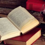 A glass of wine next to a book