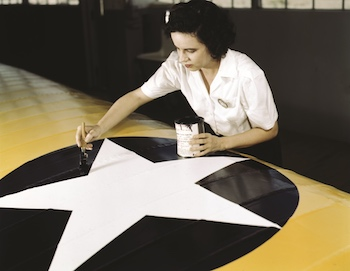 Woman painting an U.S. roundel on a fighter wing