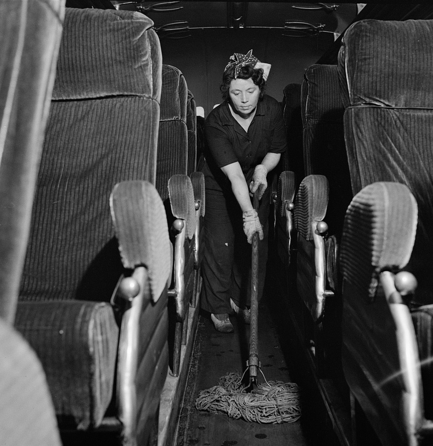 A charwoman who cleans buses mopping the floor of a bus at the Greyhound garage,