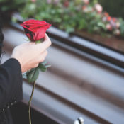 A woman holding a rose in front of a casket at a funeral.