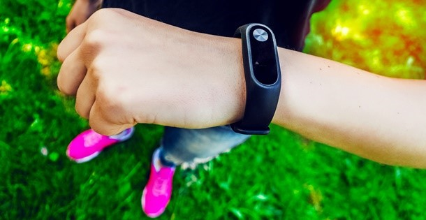 Woman's arm with a health monitoring device hung on her wrist.