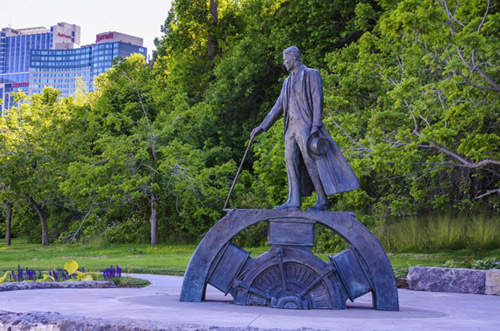 A statue of Nikola Tesla in a park near Niagara Falls. It depicts him standing on a gear while pulling a lever.
