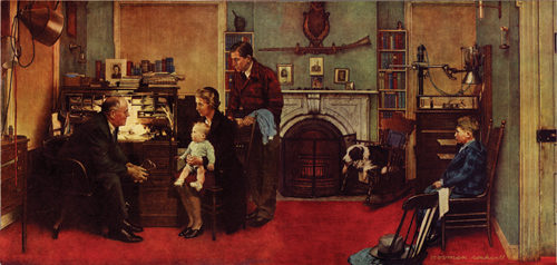 A family visits a doctor at his home office. He sits at his desk while he speaks to the family; the mother sits in the chair in front of him while holding her baby.