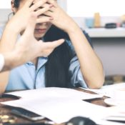 Woman with head in hands at her desk while her boss points his finger at her.