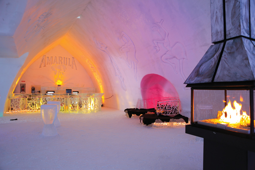 The interior of a bar made out of an igloo, complete with drinks, ice chairs, and a fireplace.