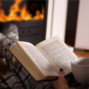 Reading a book in front of a fireplace