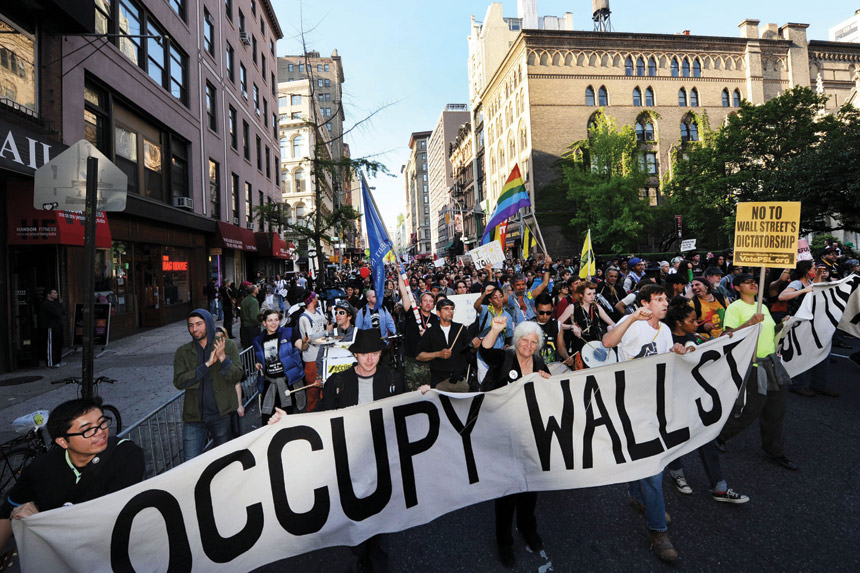 "Protesters march in lower Manhattan during an Occupy Wall Street protest, with placards reading ""No to Wall Street's dictatorship"""