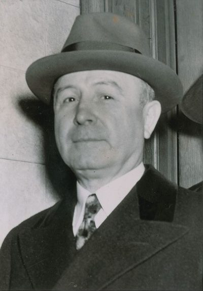 Johnny Torrio in a suit, hat, and coat.