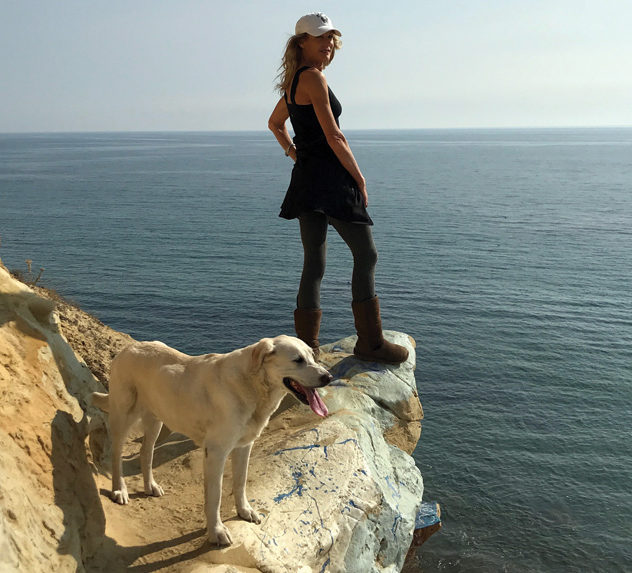 Nina Katsev and her golden lab, Calvin, on a rocky shore.