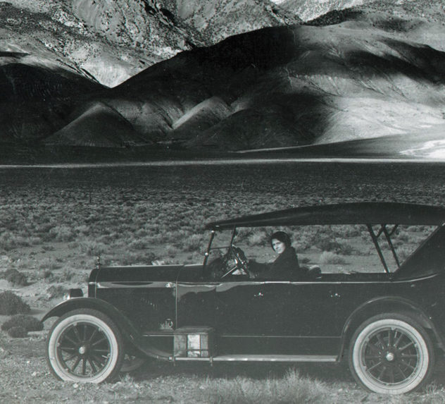 Woman driving down an early 20th century paved highway in front of the Rocky Mountains.