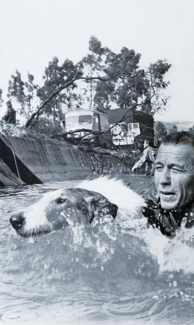 Lassie swimming in a river with fellow actor Robert Bray