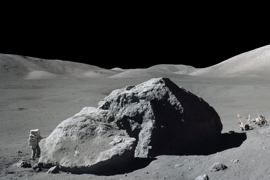 An astronaut next to a giant rock on the moon.