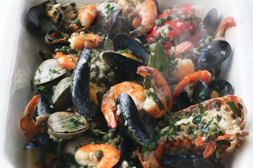 A bowl of shellfish, lemon, shrimp, and rice.