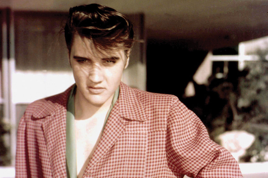 A young Elvis Presley poses for a photo wearing a red, checkered sports jacket.