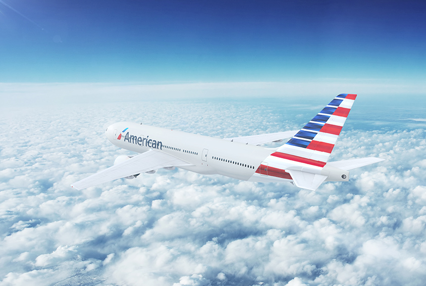 An American Airlines jetliner in flight above the clouds.