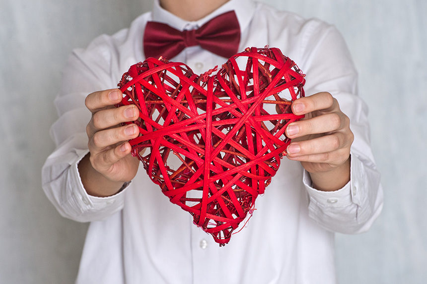 A person with a red bowtie holds a wicker Valentine heart
