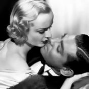 "Carole Lombard leaning in to kiss co-star, and off-screen lover, Clark Gable in the film ""No Man of Her Own"""