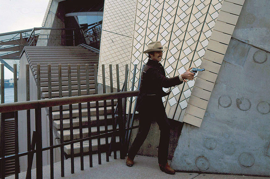 "Actor Dennis Weaver fires a pistol outside an office building during an episode of the TV western, ""McCloud""."