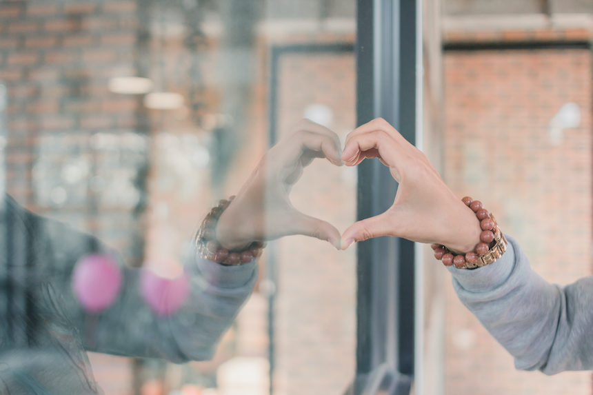 Woman forming a heart with her hand and its reflection in a glass store window.