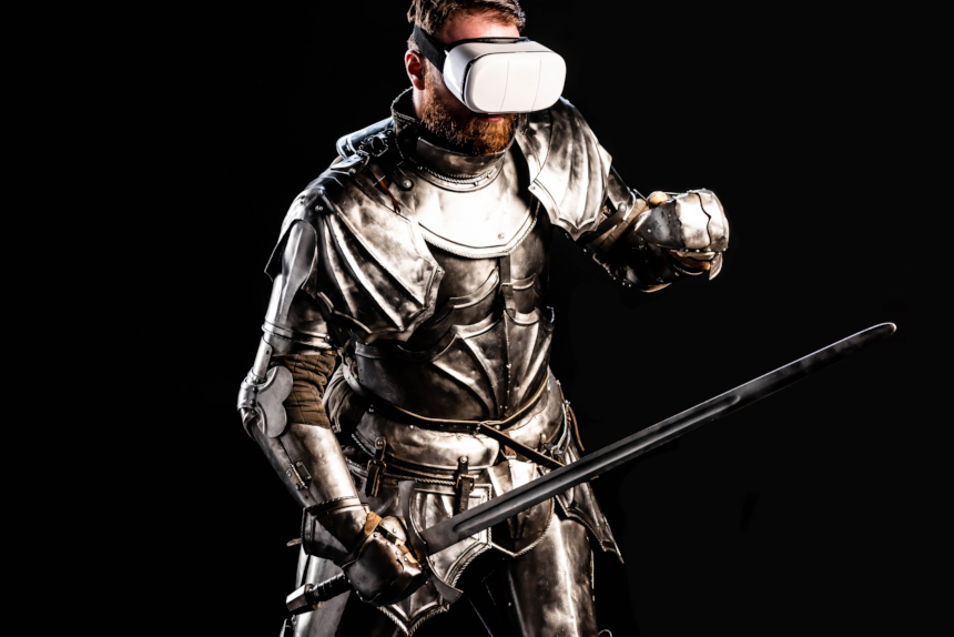 A man in a suit of armor and a medieval sword wears VR goggles.