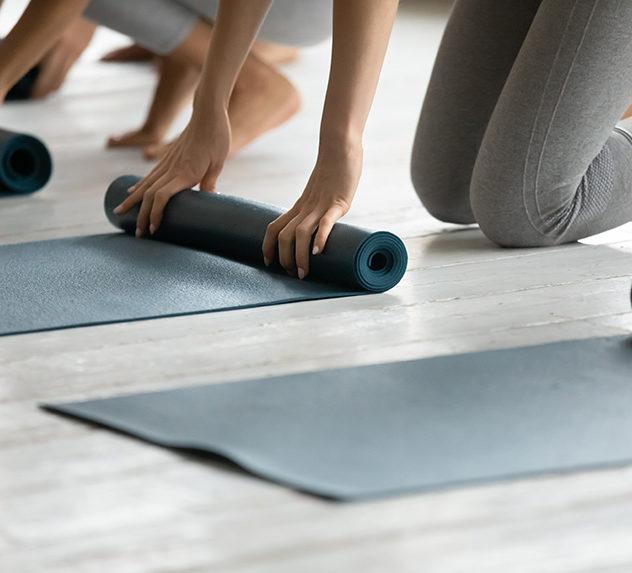 Women unrolling yoga mats