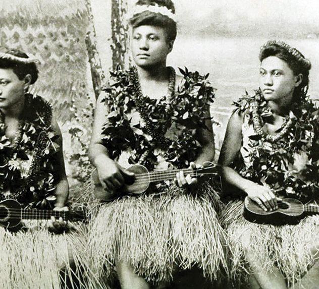 Women in traditional Hawaiian dress play their ukuleles