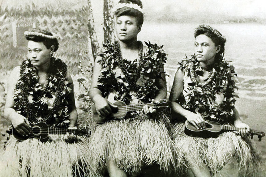 Women in traditional Hawaiian dress play their ukuleles