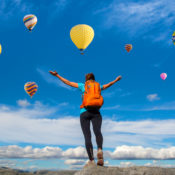 Hiker on a mountain raises their hands to greet a group of hot air balloons