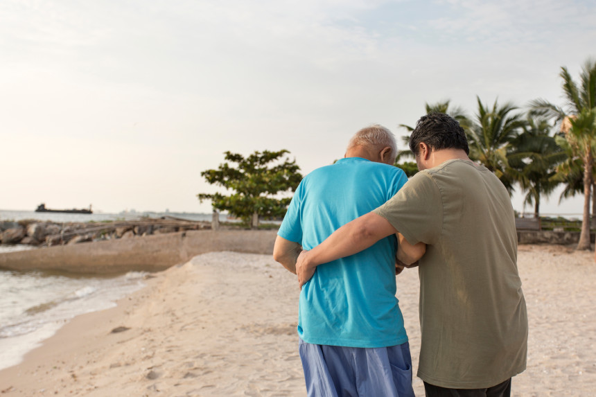 A senior citizen with Alzheimer's and his son walking together on the beach.