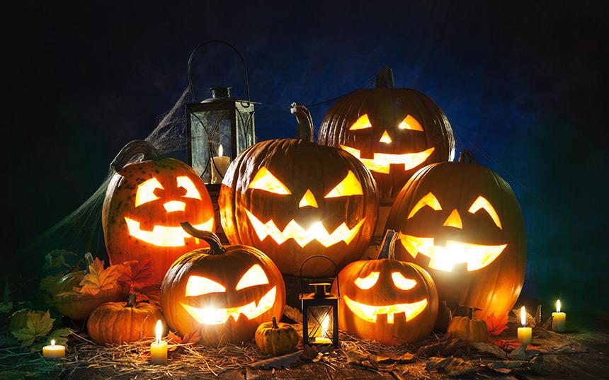 Lit Jack-O'-Lanterns grinning in the dark