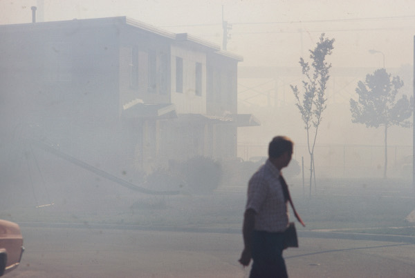 Worker walks past a smog covered row of buildings near the North Birmingham Pipe Plant