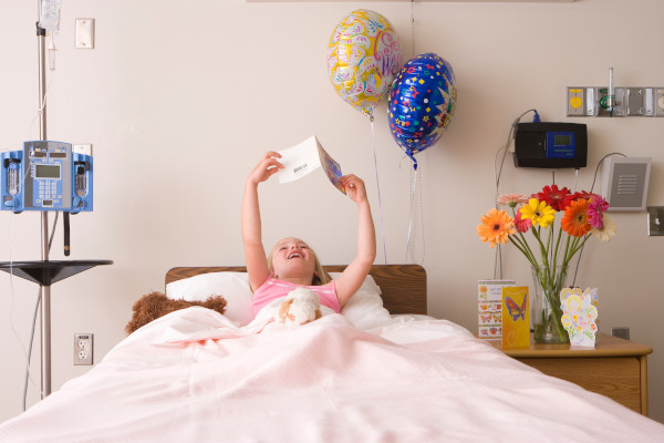A sick girl in a hospital bed reading a get well card.