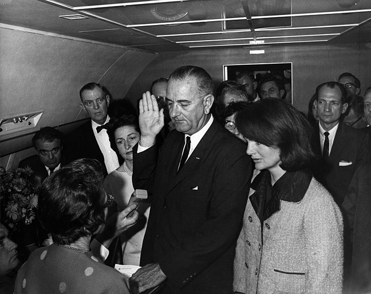 Photo of Lyndon B. Johnson taking the oath of office aboard Air Force One.