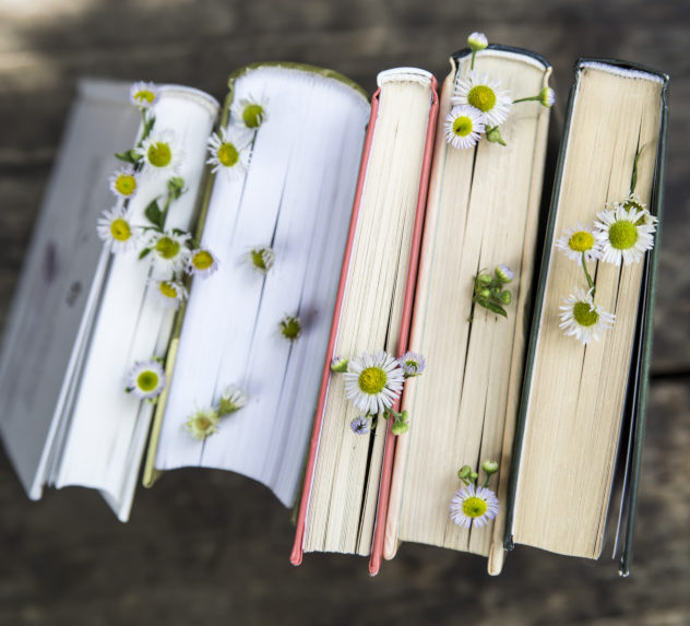 Books on a wooden table with flowers