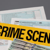 "Income tax forms with the words ""Crime Scene"" superimposed over them."