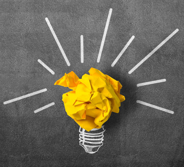 An idea bulb made out of yellow paper curled up into a ball and a chalk drawing for its base.