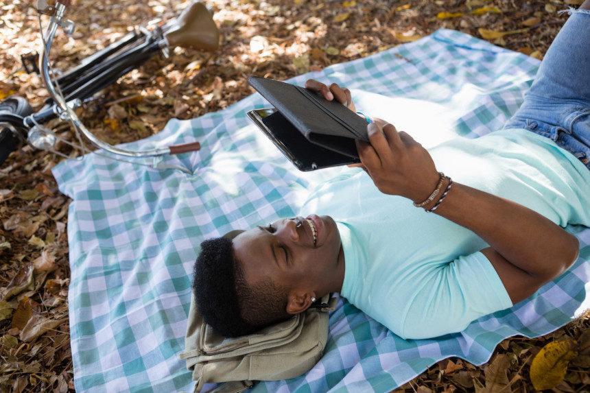 Man reading a digital tablet outside on a blanket.