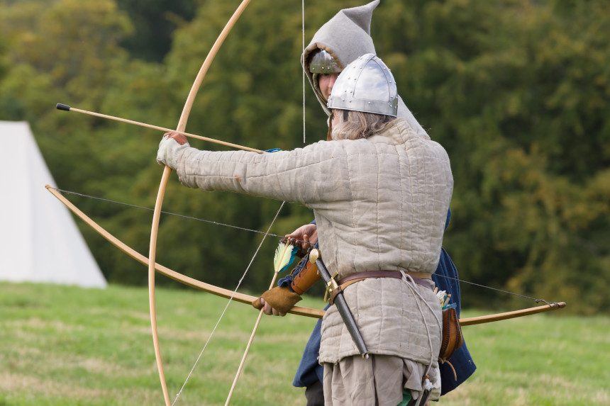 Medieval reenactors prepare to fire a bow.