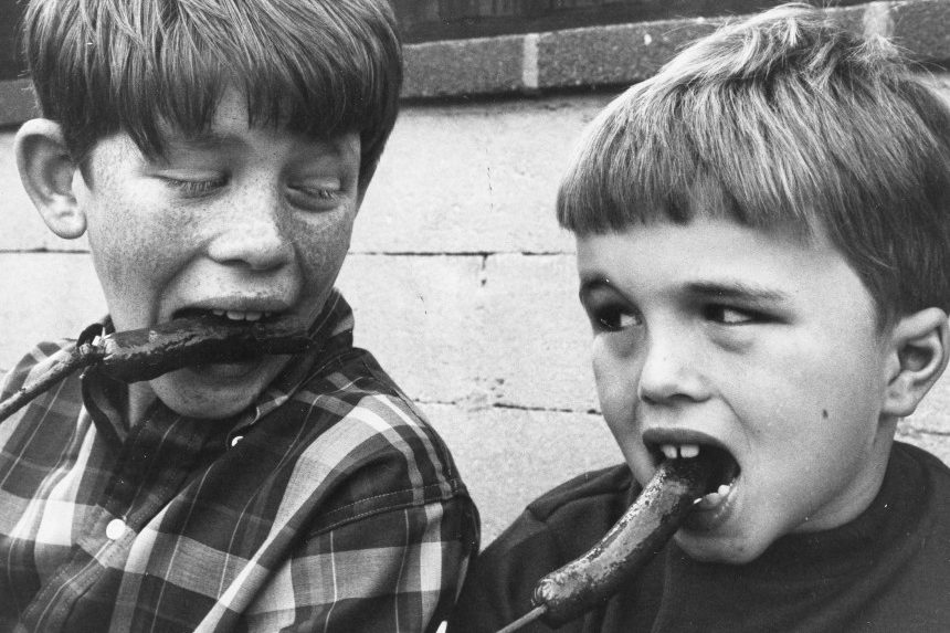 Child actors Ron Howard and Clint Howard eating hot dogs.